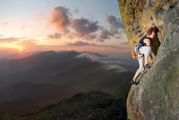岩の壁に挑戦的なルートを登る女性ロック・クライマー