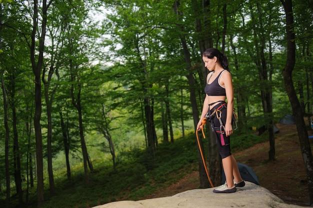 森の中のボルダーの上に立っている女性登山家