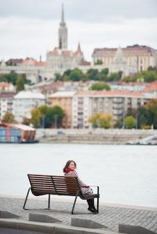 Брюнетка сидит на скамейке на набережной будапешта и оборачивается, снова глядя в камеру, вид на будайскую сторону будапешта с замком буда, матфея святого и рыбацкого бастиона