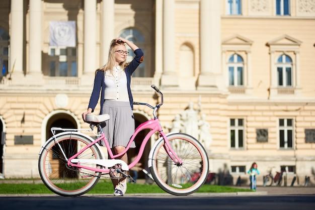 Молодая привлекательная женщина стоит держа велосипед розовой дамы на вымощенной улице города на яркий солнечный летний день на запачканной большой старой каменной предпосылке здания.