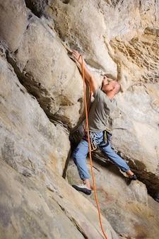 男性のリードクライマーが自然の中で大きな岩を登る。