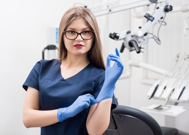 Портрет конца-вверх красивого женского дантиста на современном зубоврачебном офисе. лечение зубов