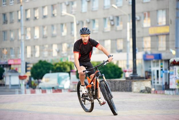 近代的な都市の建物の前で自転車に乗って若い男の自転車。屋外で運動するスポーツマンは、仕事の日の後に休憩します。健康的な生活の概念