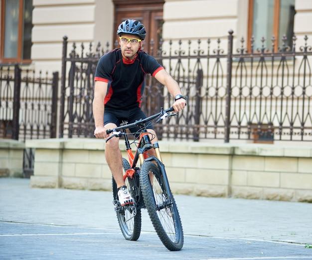 美しい建物の近くに自転車に乗ってプロのサイクリング服と保護用のヘルメットのスポーツマン。男のトレーニング、趣味の向上、コンテストの準備