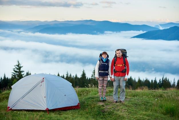 霧が横たわる強大な山々の背景をぼかした写真のテントの近くにバックパックを持つ観光客のペア。健康的なライフスタイルのコンセプト