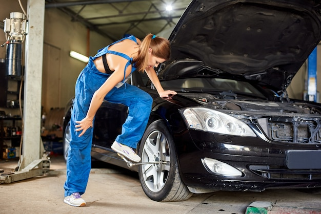 Женщина крутит ключом переднее легкосплавное колесо черного автомобиля. девушка механика в голубой рабочей форме в гараже ремонта. капот открыт в машине