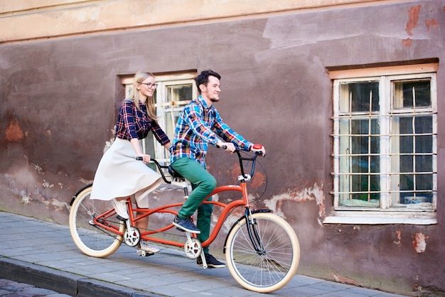 若いハンサムな男とひびの入った壁と窓に鉄の格子のある古い建物で明るい晴れた秋の日に舗装された歩道に沿ってタンデムダブル自転車に一緒に乗ってかなりブロンドの女性。