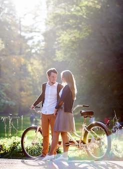 若い幸せなカップル、ひげを生やした笑みを浮かべて男と夏の公園またはぼやけた日当たりの良い緑の木の葉の森の屋外タンデムダブル自転車で立っている魅力的な女性