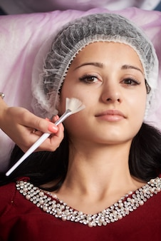 Брюнетка девушка получает лечение в салонах красоты. молодая красивая темноволосая женщина в офисе косметолога. процедура ультразвуковой очистки. аппаратная косметология. крупный план