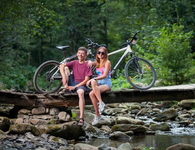 自転車の近くの川の橋の上の森で休んでカップル