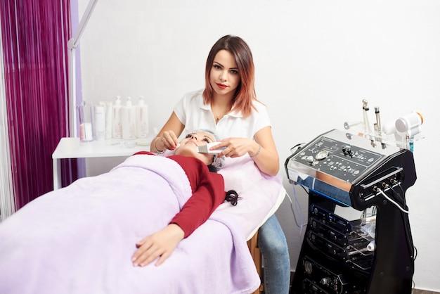 Врач с ультразвуковым скрабером проводит ультразвуковой кавитационный пилинг лица для женщины. процедура ультразвуковой чистки лица. косметологическая клиника.
