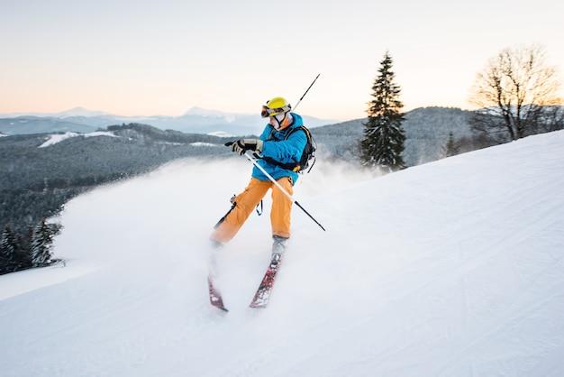 Лыжник в снегу производит торможение на склоне горы