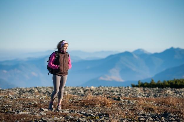 自然を楽しんでいるロッキー山脈の上を歩く婦人