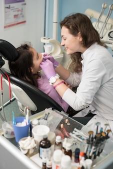 若い女性歯科医は歯科医院で患者の少女の歯を治療しています。歯科、医学、口腔病学、ヘルスケアの概念。