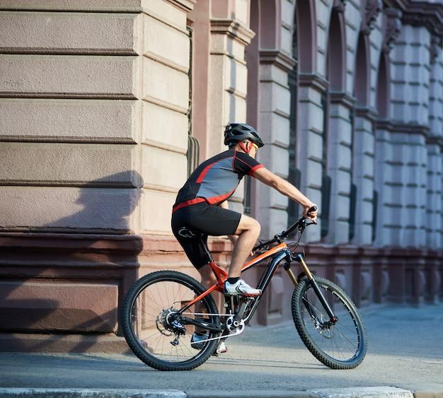 急いで建物を渡す市内中心部で自転車に乗る運動サイクリストの背面図。スポーツマントレーニング、屋外で運動。健康的なライフスタイルのコンセプト