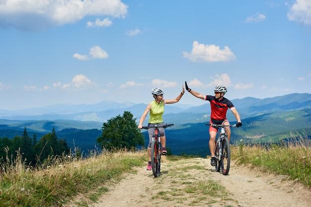 カルパティア山脈の日当たりの良い夏の日に山の道でクロスカントリー自転車に乗って幸せなカップルの自転車。アクティブな男性と女性がお互いにハイファイブを与える