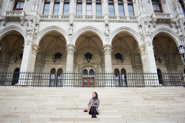Сладкая девочка сидит на ступеньках дворца парламента в будапеште, венгрия. осень