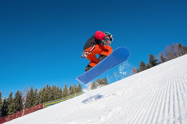 Низкий угол выстрела человека сноубордист прыгает в воздухе во время сноуборда