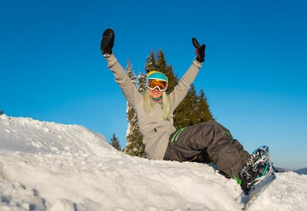 Низкий угол выстрела счастливый сноубордист молодой женщины, сидя на вершине склона