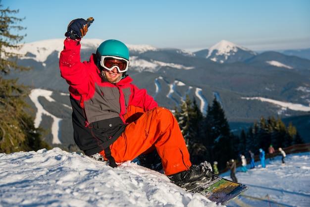 Счастливый мужской сноубордист улыбается, показывает палец вверх, сидя на снегу в горах