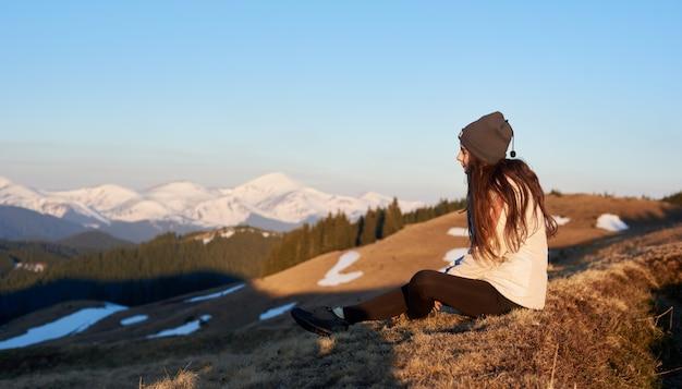 Снимок женщины, любуясь потрясающим видом, сидя на вершине горы