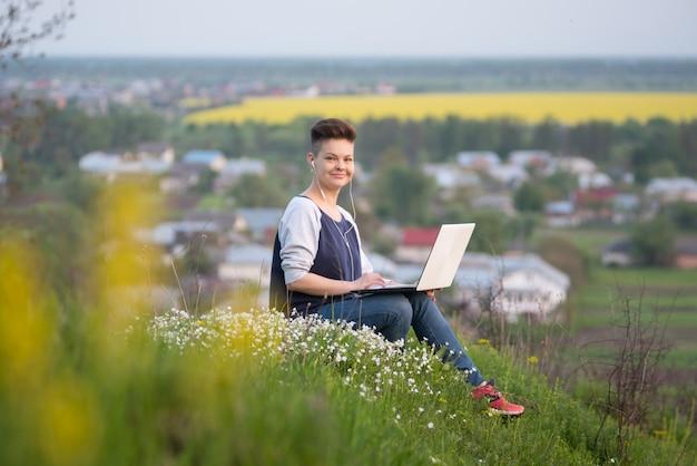 Снимок молодой женщины, сидя на вершине холма, работает на своем ноутбуке, улыбаясь в камеру
