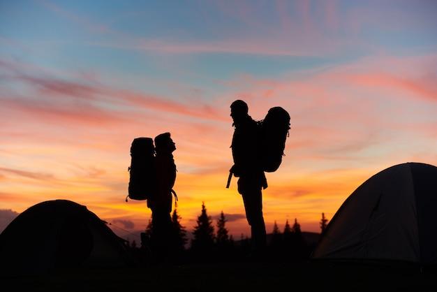 薄暗い風景を楽しんでいる岩の上にバックパックが立っているハイカーのカップルのシルエット