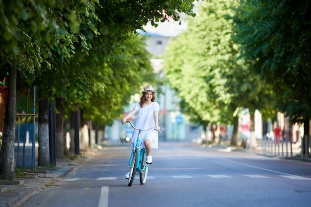 Молодая женщина едет по дороге на ретро велосипеде в летний день