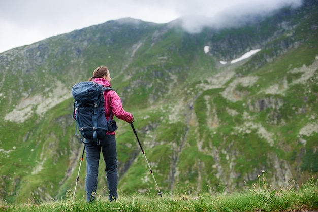 Молодая женщина турист с рюкзаком и трости, любуясь красивыми снежными скалистыми горами