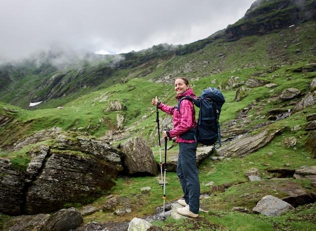 Счастливый женский турист показывает жест с пальцем класса на поход в долину гор.