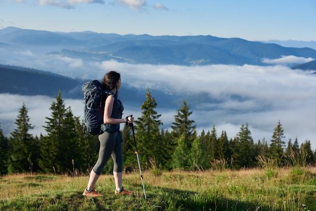 バックパックと丘の上にハイキングトレッキングポールを持つ若いスポーティな女性登山家