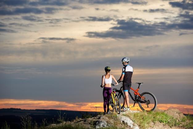 Пара стоит вместе возле горных велосипедов на скалистом холме