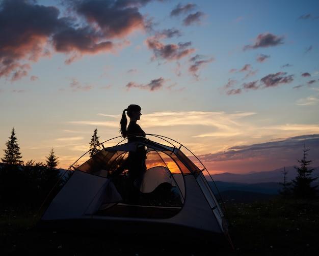 日の出の丘の上にキャンプ場で若い女性観光客のシルエットをプロファイルします。
