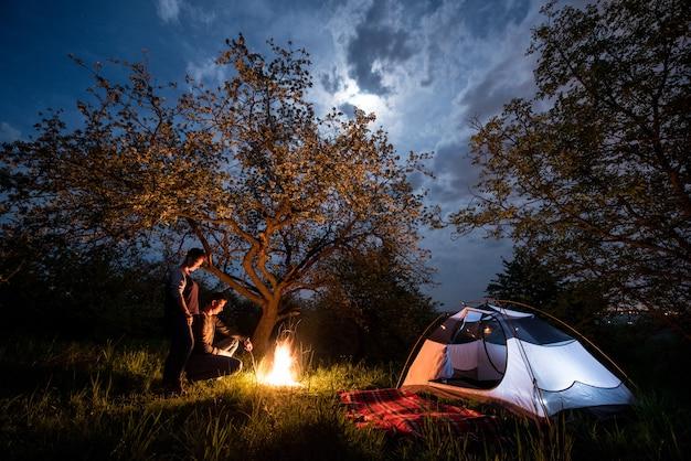 ロマンチックなカップルの観光客が木と夜空と月の下でテントの近くのキャンプファイヤーに立っています。ナイトキャンプ