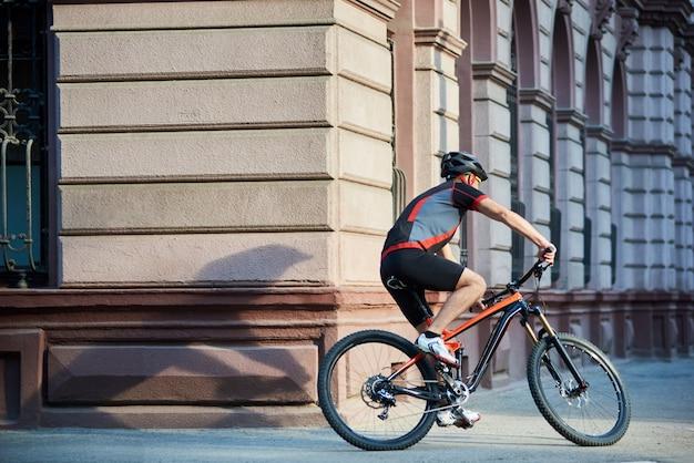 急いで建物を渡す市内中心部で自転車に乗るプロのサイクリスト。スポーツマンのトレーニング、屋外でのエクササイズ。健康的なライフスタイルのコンセプト