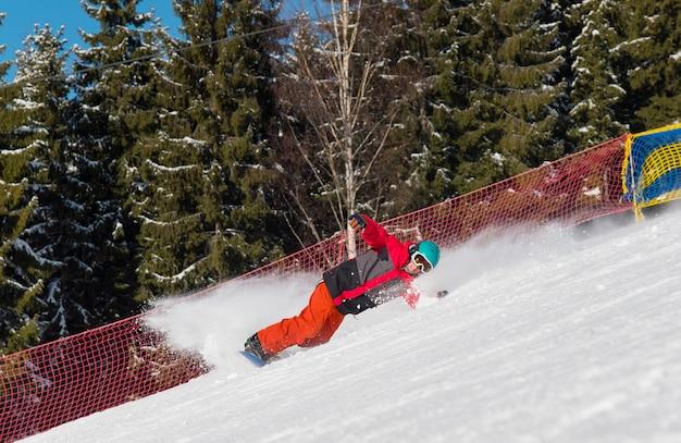 Профессиональный сноубордист едет по склону в горах.