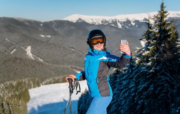 Горизонтальный снимок лыжницы, улыбаясь, используя ее смартфон, принимая фотографии
