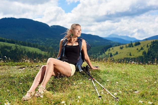 かなり笑顔の女性ハイカートレッキングスティックで草が茂った丘で休んで山道をハイキング