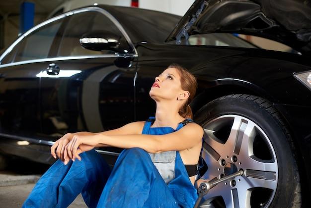 Соблазнительная девушка в синей рабочей форме сидит возле черного автомобиля в ремонтном гараже.
