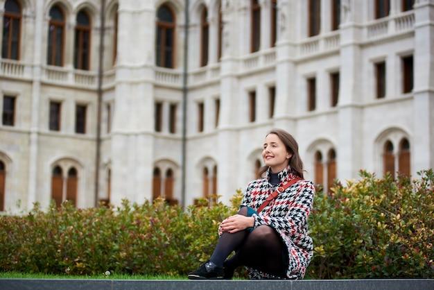 甘い笑顔の女性がブダペストの国会議事堂の緑の芝生に座っています。