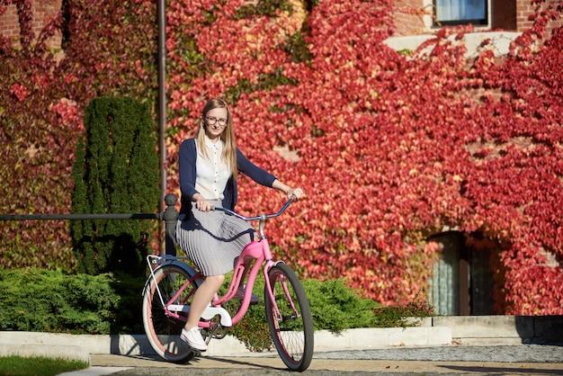 レンガ壁の明るく暖かい晴れた日にピンクの女性自転車に乗ってかなり笑顔の若い女性