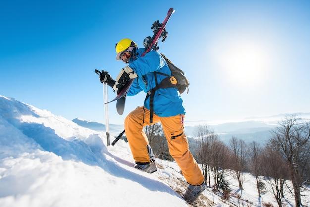 雪に覆われた丘を歩くスキーヤー