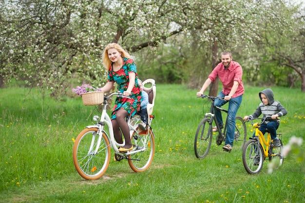 Семья с двумя детьми, езда на велосипеде в весеннем саду