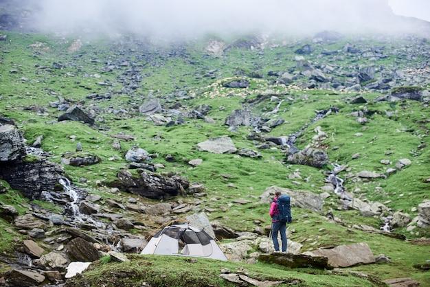 Турист возле палатки на скалистом склоне