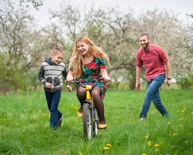 Мать учит сына кататься на велосипеде по его примеру
