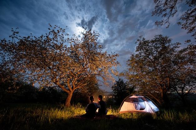 テントの近くのキャンプファイヤーで観光客