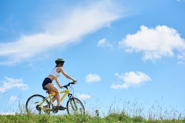 雲と青い空を背景にマウンテンバイクに乗って選手若いバイカー