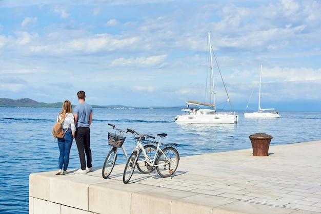 自転車に立っているバックパックを持つ観光客カップル、男女の背面図