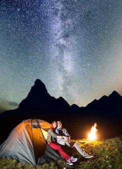 キャンプファイヤーの近くの夜のキャンプでハイカー
