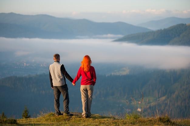 朝のもやを楽しんで、丘の上に立っている背面図カップル